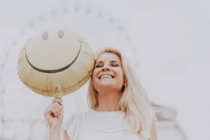 Photo: smiling woman holding a balloon